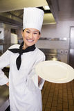 Smiling female cook holding an empty plate in kitchen Royalty Free Stock Photos