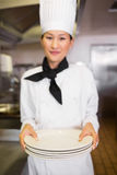 Smiling female cook holding empty plates in kitchen Royalty Free Stock Photo