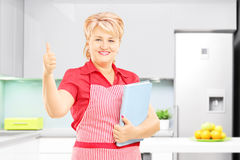 Smiling female cooker holding a cookbook and giving thumb up. Smiling mature female cooker with apron holding a cookbook and giving thumb up in her kitchen Stock Photo