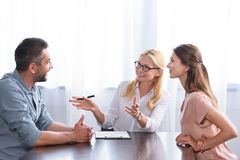 Smiling female counselor gesturing by hands and talking to couple on therapy session. In office royalty free stock photo
