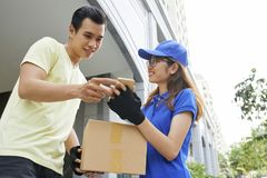 Courier showing smartphone to client stock image
