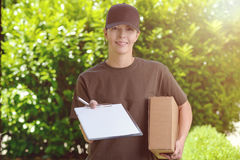 Smiling female courier delivering a parcel. Smiling attractive female courier in a cap delivering a parcel to the door of a house holding out a clipboard for royalty free stock image
