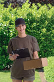 Smiling female courier delivering a parcel Royalty Free Stock Images