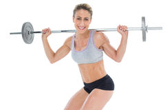 Smiling female crossfitter lifting barbell behind head looking at camera Royalty Free Stock Photo