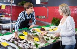 Smiling female customer choosing and buying fish Stock Image