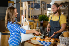 Smiling female customer interacting with staff at counter Royalty Free Stock Photos