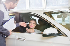 Smiling female customer receiving car key from mechanic in workshop Stock Images