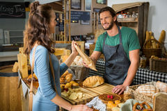 Smiling female customer receiving a parcel from bakery staff at counter. In bakery shop Royalty Free Stock Images