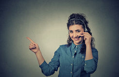 Smiling female customer representative with phone headset pointing at copy space. Closeup portrait of beautiful, adorable smiling female customer representative Royalty Free Stock Images