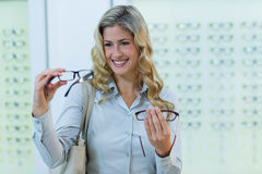 Smiling female customer selecting spectacles Stock Photo