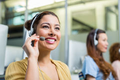 Smiling female customer service executive talking on headset at desk Royalty Free Stock Photo