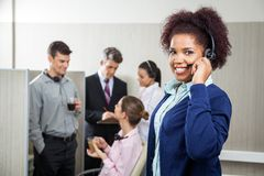 Smiling Female Customer Service Representative. Portrait of smiling female customer service representative holding headphones while manager discussing with royalty free stock photo