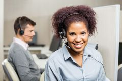 Smiling Female Customer Service Representative In. Portrait of smiling female customer service representative with male colleague in background at office royalty free stock photos