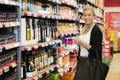 Smiling Female Customer Standing In Supermarket Royalty Free Stock Photography