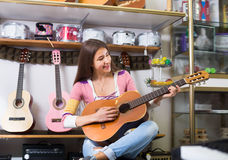 Smiling female customer trying to play guitar Royalty Free Stock Image