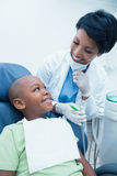 Smiling female dentist examining boys teeth Stock Photo