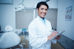 Smiling female dentist holding clipboard Royalty Free Stock Images