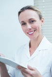 Smiling female dentist holding clipboard Stock Images