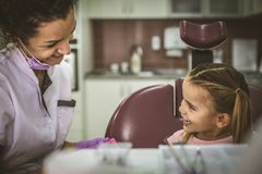 Smiling female dentist make fun with little girl at office. stock photos