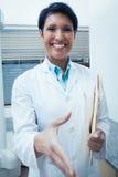 Smiling female dentist offering handshake Stock Images