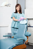 Smiling Female Dentist Standing By Dental Chair At Stock Photography