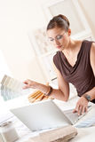 Smiling female designer with color swatch. And laptop at office royalty free stock photos
