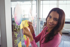 Smiling female designer holding adhesive note on glass in creative office Royalty Free Stock Photos