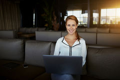 Smiling female designer using laptop computer for creates opening inauguration for new restaurant, Royalty Free Stock Photos