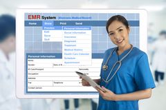 Female doctor with tablet showing electronic medical record system on screen behind. royalty free stock images