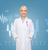 Smiling female doctor with cancer awareness ribbon Stock Photo