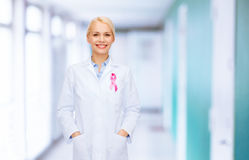 Smiling female doctor with cancer awareness ribbon Royalty Free Stock Photos