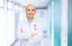 Smiling female doctor with cancer awareness ribbon. Healthcare and medicine concept - smiling female doctor with pink cancer awareness ribbon over hospital royalty free stock photography