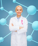 Smiling female doctor with cancer awareness ribbon Stock Image