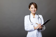 Smiling female doctor with clipboard Stock Images