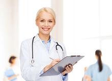 Smiling female doctor with clipboard Royalty Free Stock Image