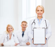 Smiling female doctor with clipboard Stock Photos