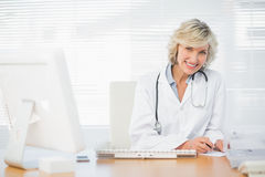 Smiling female doctor with computer at medical office Stock Image