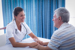 Smiling female doctor consoling senior man Royalty Free Stock Photos