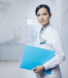 Smiling female doctor with file Stock Photos