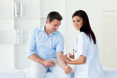 Smiling female doctor giving vaccine to a patient Stock Photos