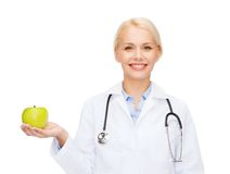 Smiling female doctor with green apple Stock Photos