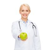 Smiling female doctor with green apple Stock Photo