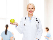 Smiling female doctor with green apple Stock Photography