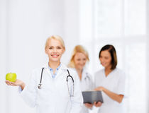 Smiling female doctor with green apple Royalty Free Stock Photos
