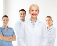 Smiling female doctor with group of medics Royalty Free Stock Image