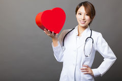 Smiling female doctor with heart. Smiling asian female doctor with heart royalty free stock image