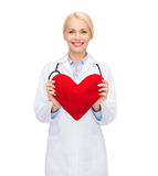Smiling female doctor with heart and stethoscope Stock Image