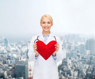 Smiling female doctor with heart and stethoscope Stock Photos