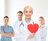 Smiling female doctor with heart and stethoscope Stock Photography