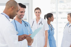 Smiling female doctor and her colleagues Stock Images